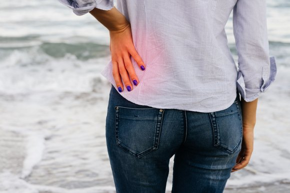 Lady holding her lower back because of lower back pain