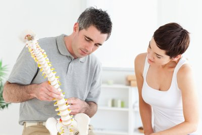Chiropractor explaining about spinal chord to his patient