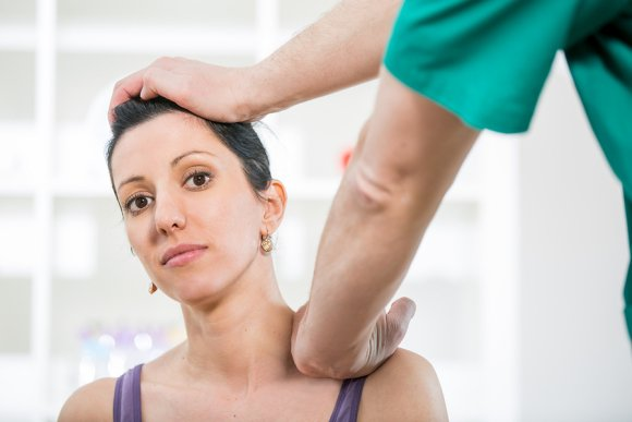 Chiropractor giving treatment to a lady